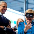 U.S. President Barack Obama looks on as German Chancellor Angela Merkel tests VR goggles when touring the Hannover Messe, the world's largest industrial technology trade fair, in Hannover. Photo: AP