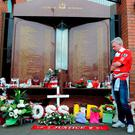A Liverpool fan looking at tributes at the Hillsborough memorial at Anfield, Liverpool Credit: Martin Rickett/PA Wire