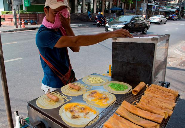 A street vendor wipes the sweat from his face as he cooks food in central Bangkok, Thailand (AP Photo/Mark Baker)