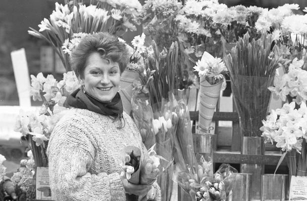 Barbara Brannigan from East Wall, Dublin purchasing tulips in Moore St, Dublin in Feb 1986 (Part of the Independent Newspapers Ireland/NLI Collection)