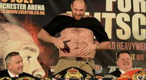 British heavyweight boxer Tyson Fury (C) gestures as he removes his t-shirt during a press conference to publicise his forthcoming world heavyweight title fight against Ukranian heavyweight Wladimir Klitschko