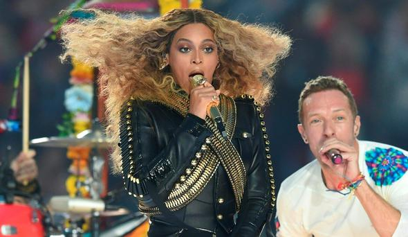 (FILES) This file photo taken on February 7, 2016 shows Beyonce and Chris Martin as they perform during Super Bowl 50 between the Carolina Panthers and the Denver Broncos at Levi's Stadium in Santa Clara, California. Streaming site Tidal has soared in popularity since Beyonce released her latest album through the service as an exclusive, although she made it available on iTunes as well on April 25, 2016. The pop superstar late Saturday released her sixth album,