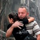 A man carries a child after airstrikes hit Aleppo, Syria