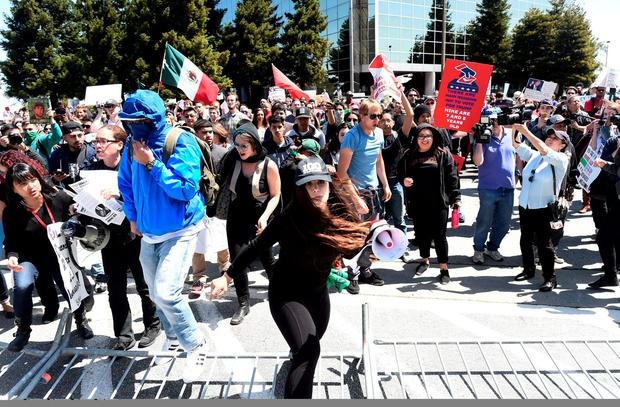 Protesters make their way over a barricade as they demonstrate against U.S. Republican presidential candidate Donald Trump outside the Hyatt hotel where Trump was speaking at the California GOP convention in Burlingame, California April 29, 2016. REUTERS/Noah Berger