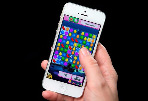 A woman plays Candy Crush on a smartphone. Photo: Reuters