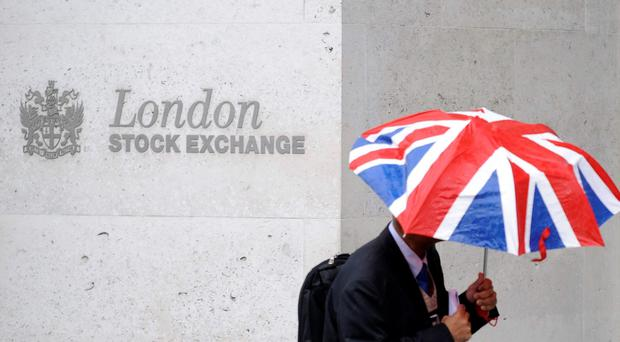 A worker shelters from the rain as he passes the London Stock Exchange in the City of London. Photo: Reuters