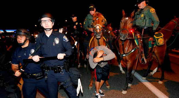 Police break up a group of demonstrators outside Republican presidential candidate Donald Trump's rally in Costa Mesa, California. Photo: Reuters
