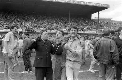 CATASTROPHE: An injured fan receiving attention on the pitch as the disaster in Hillsborough unfolded. Photo: PA