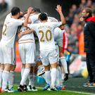 Swansea's Jack Cork celebrates scoring their second goal with team mates as Liverpool manager Juergen Klopp looks on