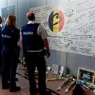 Police officers stand in front of a tribute to the victims in the departure hall after a ceremony at Brussels Airport as it reopens 40 days after deadly attacks in Zaventem, Belgium, May 1, 2016