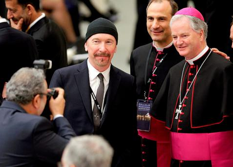U2 guitarist David Evans, also known by his stage name The Edge, poses with Irish bishop Paul Tighe (R) before listening to U.S. Vice President Joe Biden in Paul VI hall at the Vatican April 29, 2016