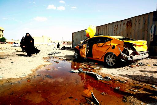 TOPSHOT - Iraqi women walk past a damaged car following a twin suicide bombing attack, claimed by the Islamic State (IS) group, in the southern Iraqi city of Samawah, situated deep in Iraq's Shiite heartland, on May 1, 2016