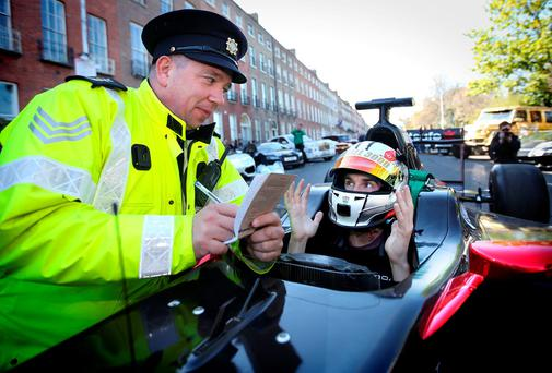 Sgt Neill Crowley pretends to write a ticket for professional driver Ollie Webb in his F1 car as cars gather for Gumball Rally, which was started by David Hasselhoff. Photo: Gerry Mooney