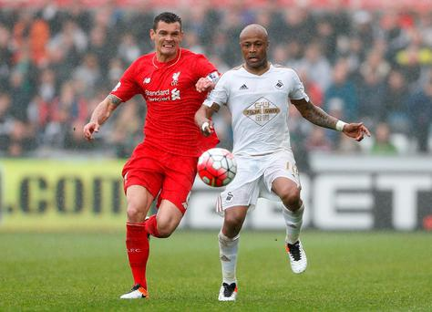 Liverpool's Dejan Lovren and Swansea's Andre Ayew compete for possession during the Premier League clash. Photo: Carl Recine/Reuters