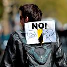 A protester carries a backpack bearing a placard reading 'No to the labour law, No thank you!'. Photo: Getty