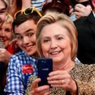 Democratic presidential candidate Hillary Clinton takes photographs with audience members during a campaign stop in Indianapolis, Sunday, May 1, 2016