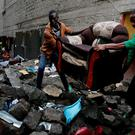 People carry a sofa as they leave the Huruma neighbourhood during the search for residents feared trapped in the rubble of a six-storey building that collapsed after days of heavy rain, in Nairobi, Kenya May 1, 2016