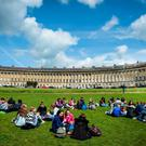 People picnic on the grass in front of the Royal Crescent, Bath, as London will be hotter than Ibiza this weekend, with scorching temperatures of up to 23 degrees. Photo: Ben Birchall/PA Wire