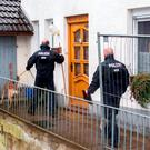Two policemen with a dog arriving at a house in Hoexter, northwestern Germany, where used to live a man and his ex-wife suspected of having kidnapped, abused and killed a woman. Photo: Marcel Kusch/AFP/Getty Images