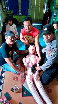 Policemen posing with a sex doll in Banggai in Sulawesi.