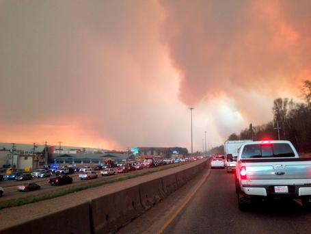 Smoke from a wildfire rises in the air as cars line up on a road in Fort McMurray, Alberta (Greg Halinda/The Canadian Press via AP)