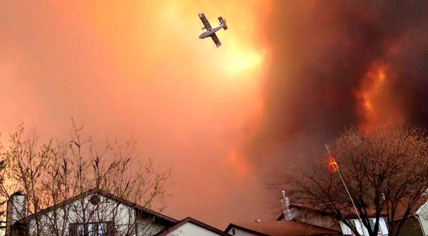 Smoke fills the air as a small plane flies overhead in Fort McMurray, Alberta. (Kitty Cochrane/The Canadian Press via AP)