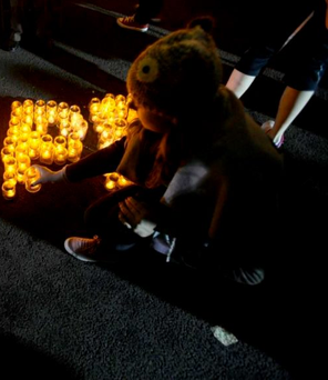 A participant lighting candles at a Darkness into Light event last year