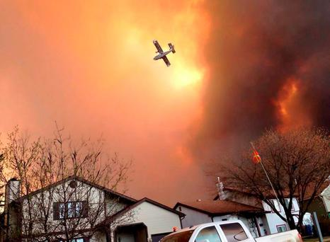 Smoke fills the air as a small plane flies overhead in Fort McMurray, Alberta (Kitty Cochrane/The Canadian Press via AP)