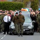 A guard of honour flanks the coffin of Michael Barr at his funeral in Strabane Co Tyrone this morning. Barr was shot dead at the end of April in a pub in Dublin. PACEMAKER BELFAST