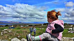 Róisín Ní Mhárta watches her brothers and cousin playing in the fields on a Connemara Sunday. Máirín Ní Mhárta