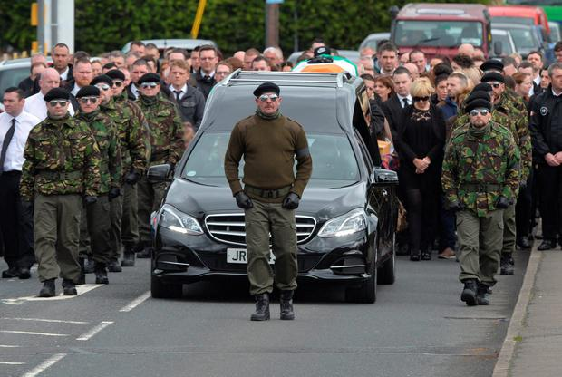 The funeral cortege is flanked by dozens in paramilitary uniform