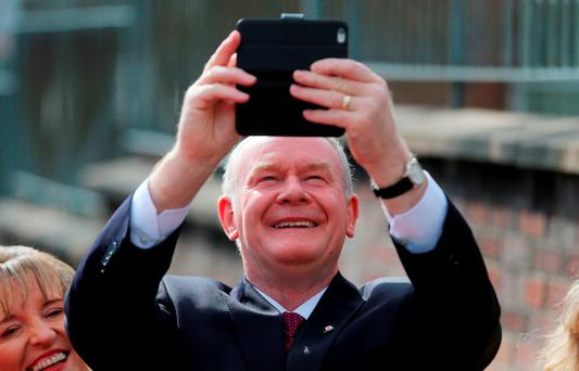 Sinn Fein's Martin McGuinness takes a photo of the waiting media as he casts his vote at the Model Primary School in Derry, as polls open for the Stormont Assembly election. Photo: PA