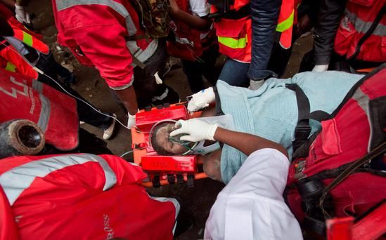 A woman is carried away on a stretcher by medics as she is rescued after being trapped for six days in the rubble of a collapsed building, in the Huruma area of Nairobi, Kenya. Photo: AP