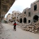 A boy rides a bicycle near damaged buildings in the rebel held area of Old Aleppo. Photo: Reuters