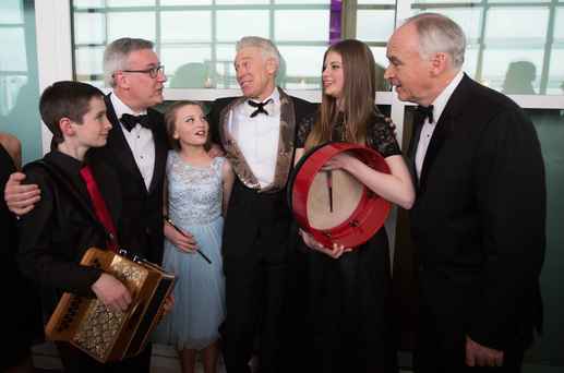Young musicians from Music Generation, Ireland's national music program, speak with Kieran McLoughlin, president and CEO of The Worldwide Ireland Funds (second from left), U2's Adam Clayton, and John Fitzpatrick, chairman of The American Ireland Fund (right), during The American Ireland Fund New York Dinner Gala on May 5, 2016 in New York City. Photo: Michael Nagle
