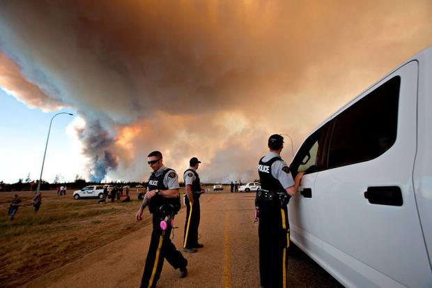 Police officers direct traffic under a cloud of smoke from a wildfire in Fort McMurray, Alberta, Friday, May 6, 2016. (Jason Franson/The Canadian Press via AP)