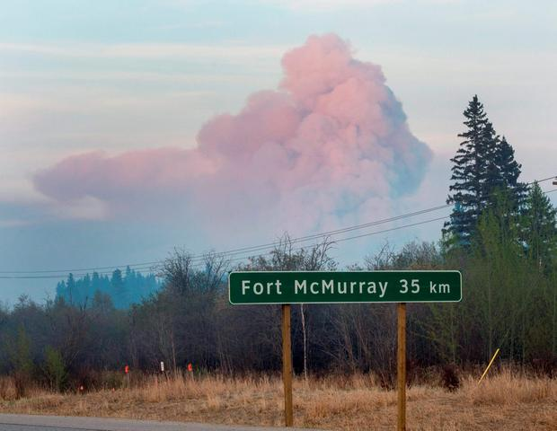 A massive plume of smoke rises from a wildfire burning out of control near the highway to Fort McMurray, Alberta, Friday, May 6, 2016. (Ryan Remiorz/The Canadian Press via AP)