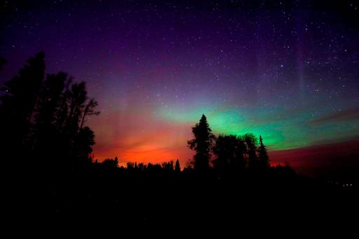 The wildfires glow underneath The Northern Lights, also known as the Aurora Borealis, near Fort McMurray, Alberta, Canada, May 7, 2016. REUTERS/Mark Blinch