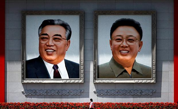 A woman is dwarfed as she walks past giant portraits of the late North Korean leaders Kim Il Sung, left, and Kim Jong Il at the Kim Il Sung Square Saturday, May 7, 2016 in Pyongyang, North Korea. (AP Photo/Wong Maye-E)