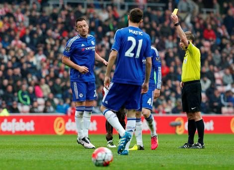 Referee Mike Jones shows Chelsea's John Terry a yellow card Reuters / Russell Cheyne