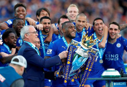 Leicester City's Wes Morgan and manager Claudio Ranieri lift the trophy as they celebrate winning the Barclays Premier League. Photo: Carl Recine/Reuters