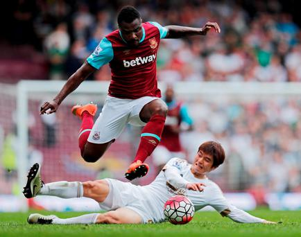 Swansea's Ki Sung Yueng tackles West Ham's Emmanuel Emenike. Photo: Eddie Keogh/Reuters