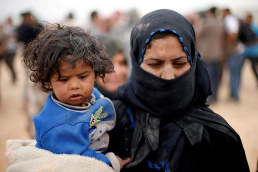 GRIM: A Syrian refugee woman, who is stuck between the Jordanian and Syrian borders, holds her child as she waits to cross into Jordanian territory, near the town of Ruwaished, at the Hadalat area, east of Amman. Photo: Muhammad Hamed/Reuters