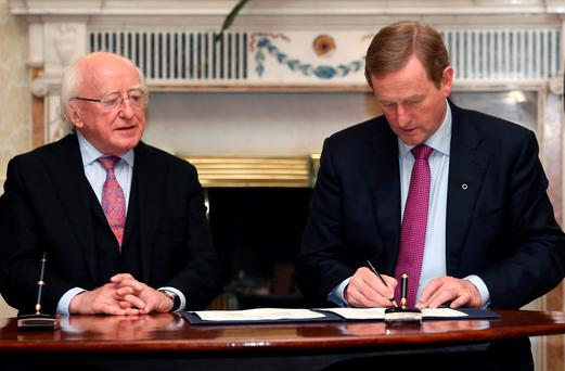 Taoiseach Enda Kenny signing the 32nd Dail into office alongside President Michael D Higgins Photo: Colin Keegan, Collins Dublin