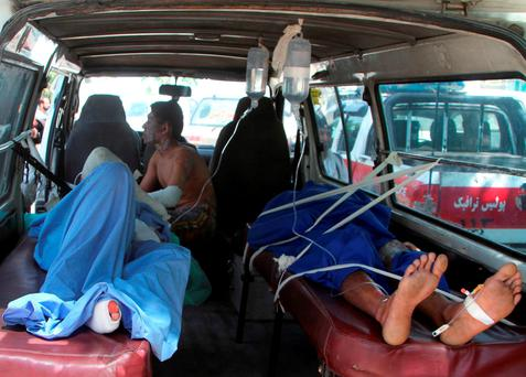 Injured Afghan men lie in an ambulance after an accident on the main highway linking the capital, Kabul, to the southern city of Kandahar, in Ghazni province eastern of Kabul, Afghanistan, Sunday, May 8, 2016. (AP Photo/Rahmatullah Nikzad)