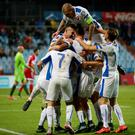 Slovakia's midfielder Robert Mak is congratulated by team mates after scoring