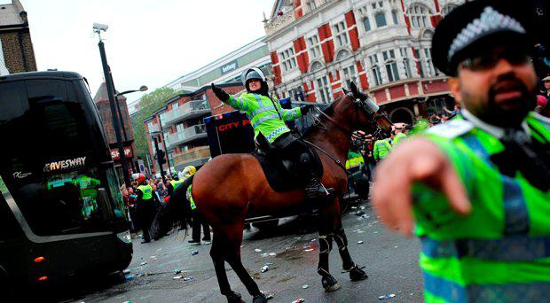 Police try to control West Ham fans gathered near 'The Champions' statue outside the Boleyn Ground on May 10, 2016 in London, England