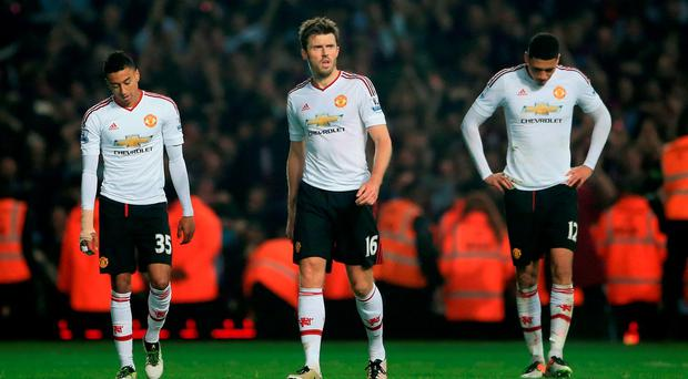 Manchester United's Michael Carrick (centre) looks dejected after the final whistle alongside teammates Jesse Lingard (left) and Chris Smalling during the Barclays Premier League match at Upton Park