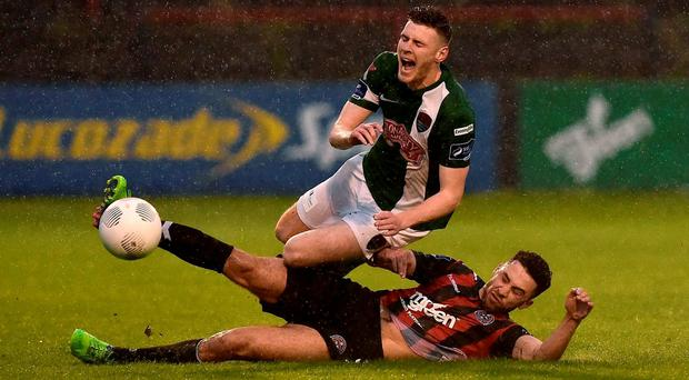 Bohemians' Roberto Lopes slips in to tackle Cork City's Garry Buckley during last night's Airtricity League clash at Dalymount Park. DAVID MAHER / SPORTSFILE