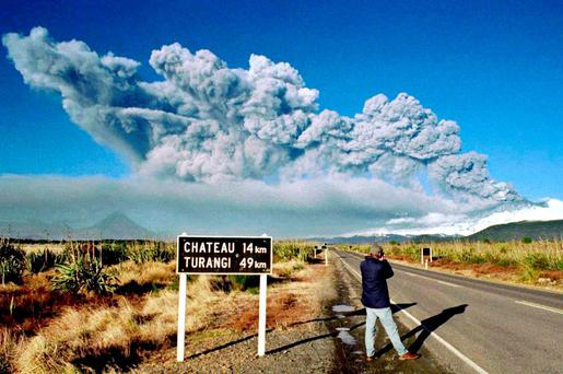A tourist takes pictures of Mount Ruapehu as it erupts on June 18, 1996 in Tongariro National Park on the central North Island of New Zealand. REUTERS/Stringer/File Photo